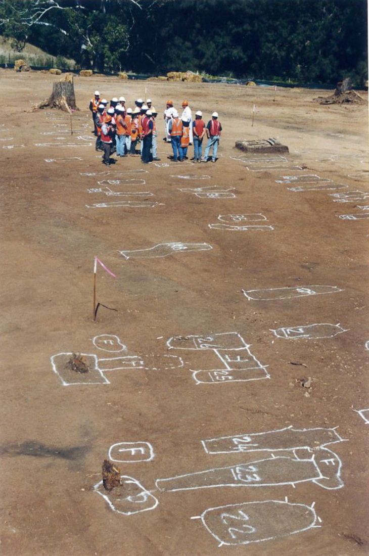 The stripping of topsoil by machine revealed the changes in soil colour and texture for each grave cut, here marked out with survey paint. Before any hand digging of individual graves, a multi-denominational service was held to give blessing for the project (Tony Jenner, 1998).